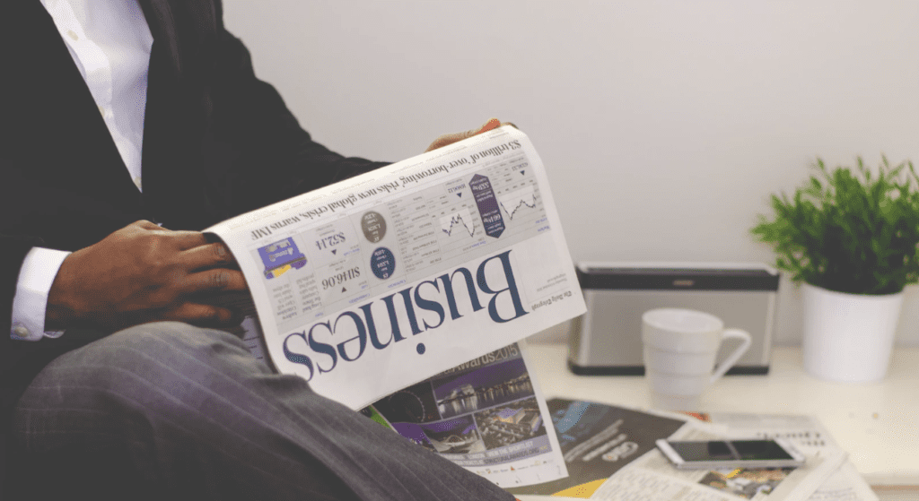 independent consultant in business attire reading business section of a newspaper