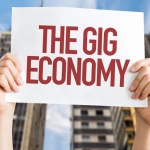 """hands holding up a sign saying """"the gig economy"""""""