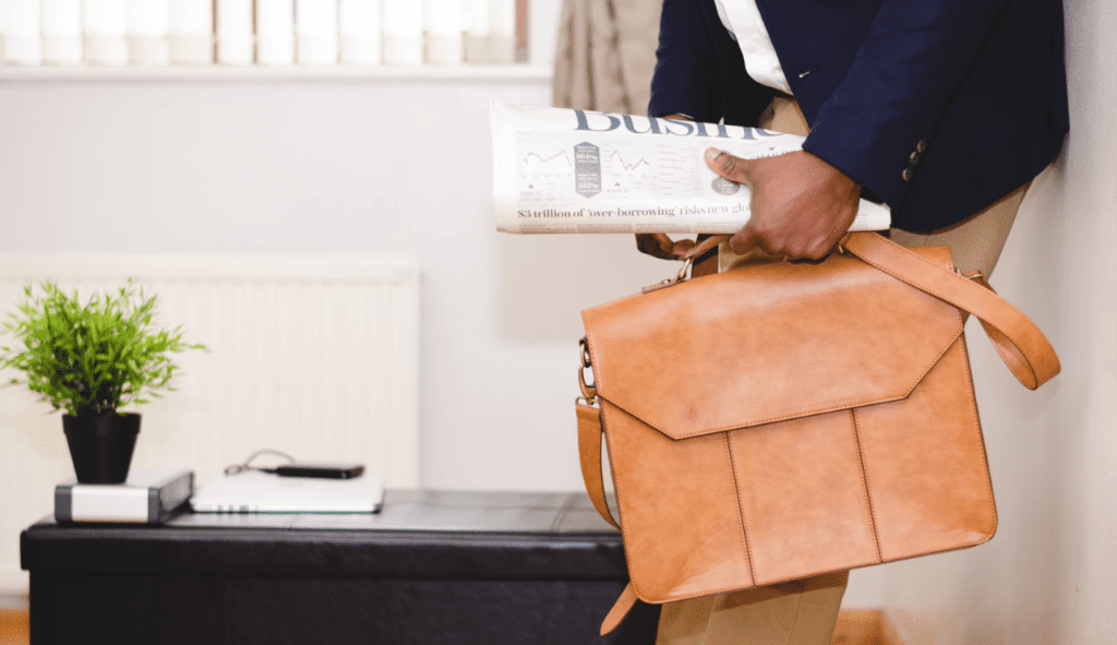 successful consultant leaving home with leather briefcase and paper in hand