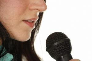 Woman's Mouth to Microphone Close-up --- Image by © Ocean/Corbis